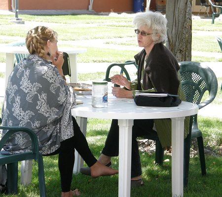 Conference participant meets with faculty member CD Wright