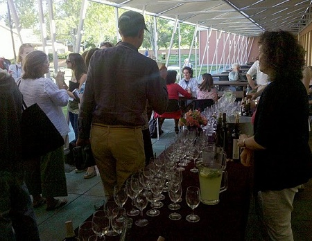 A volunteer staffs the wine table at the conference